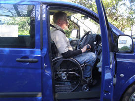 Seated in wheelchair, in the driver's position